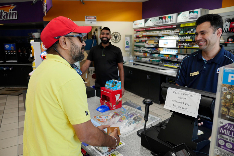 Chevron convenience store clerk assisting customer